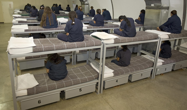 Female detainees turn their backs to the