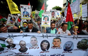 Palestinian protesters hold banners during a demonstration in solidarity with Palestinian prisoners on hunger strike in Israeli jails,